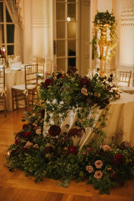 wedding reception sweetheart table moody burgundy flowers greenery draping cascading down linens