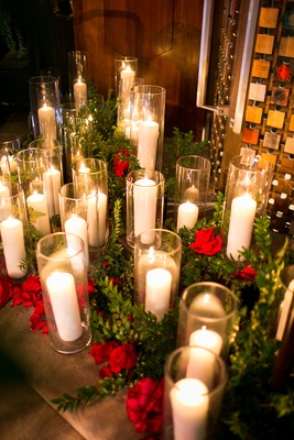 Red flowers and greenery around candles in hurricane vases on floor of temple Jewish wedding