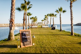 chalkboard wedding welcome sign, cabo san lucas destination wedding, palm trees, lawn
