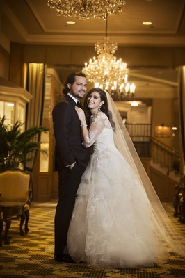 bride in lace vera wang ball gown, cathedral veil, groom in tuxedo