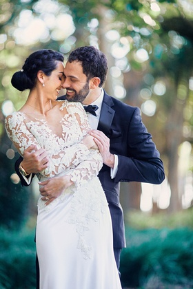 bride in pronovias wedding dress with lace bodice, crepe skirt, groom in tuxedo, bride with braid