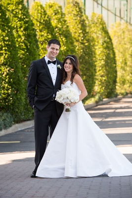 Bride in strapless a-line wedding dress by oscar de la renta with white bouquet hair down headband