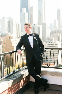 Groom in tuxedo jacket bow tie with Chicago skyline in background