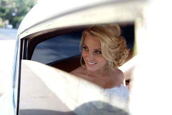 Bride with updo in classic white wedding car