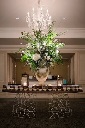 large white vase with greenery and white flowers on escort card table