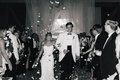 Black and white photo of bride and groom in white tuxedo jacket walk away from reception toss