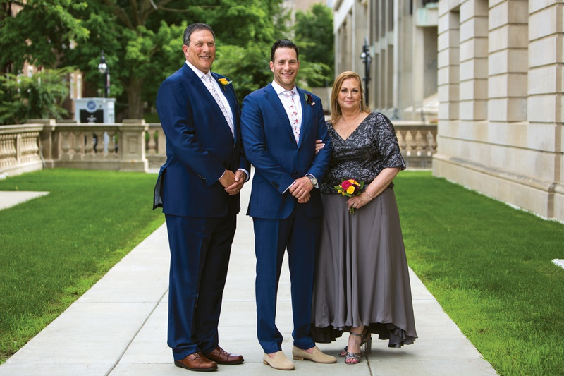 groom on sidewalk standing in between his father in navy suit, mother in grey dress & small nosegay