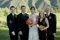 Bride in a lace Monique Lhuillier gown and groom in a black tuxedo with family