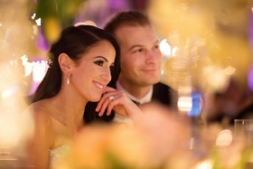 Bride and groom smiling at sweetheart table