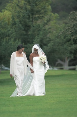 Bride holds mom's hand while walking on grassy resort grounds