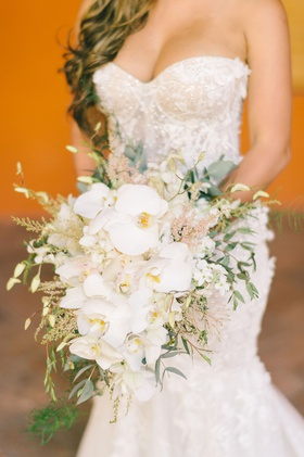 bride in strapless dress long ponytail bouquet with white phalaenopsis orchids greenery pink astilbe