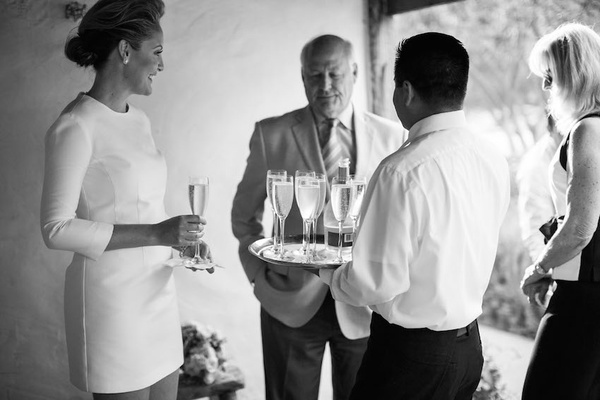Black and white photo of bride in a mini mod dress with 3/4 sleeves having Champagne with guests