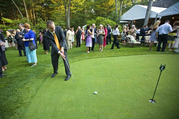 Male guest putts golf ball during outdoor cocktail hour