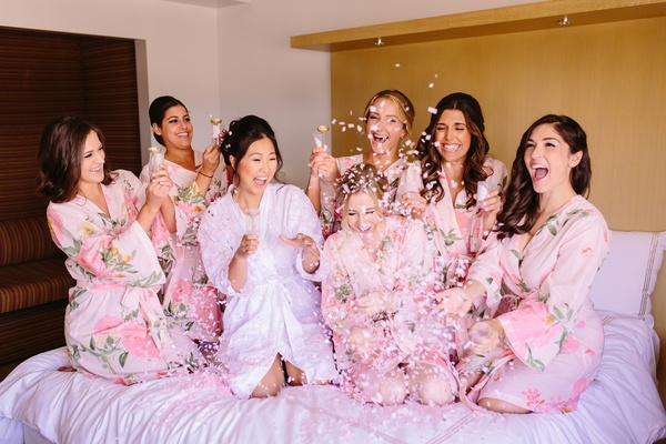 pink confetti poppers, pink bridesmaids robes with bride on bed getting ready shot
