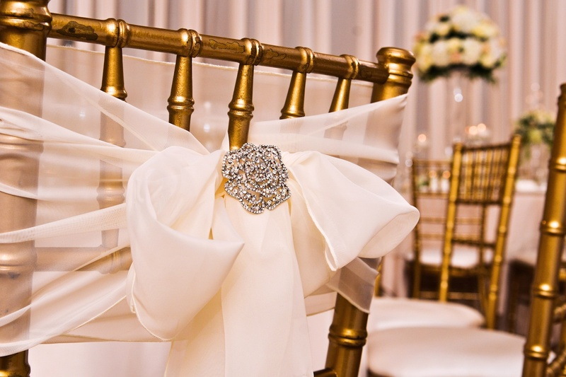 Gold chairs with sheer white bow and crystal brooch