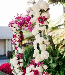 wedding ceremony arch with white flowers hydrangeas greenery and pink Bougainvillea flowers outdoor
