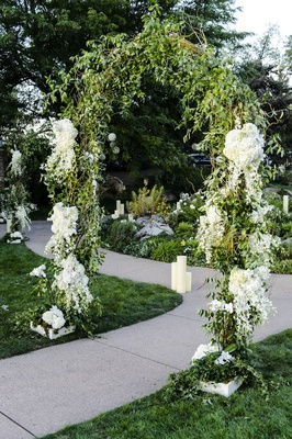 Greenery and flower arch outside on walkway to tent