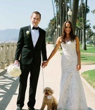Groom in a black tuxedo, bride in an Alencon lace dress with dog wearing a white flower on collar
