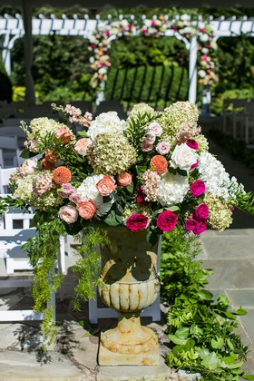 wedding ceremony decor stone urn with greenery pink orange white flowers rose hydrangea blooms