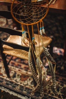 Wedding reception chair with tan dreamcatcher with blue beads, brown and white feathers