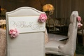 Tufted bride and groom seating at reception with signs