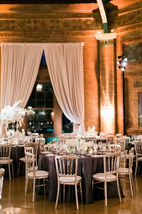 Round tables with silver chairs purple linens white centerpiece flowers brick drapery