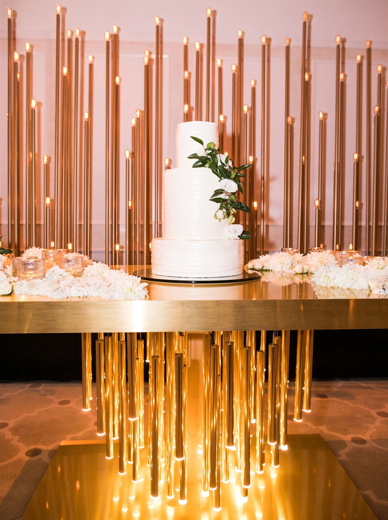 wedding cake white with white flowers greenery on luxury gold table with lighting element modern