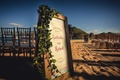 a couples colorful ceremony sign greenery for their destination wedding in cabo san lucas mexico