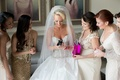 Bride in Ines Di Santo wedding dress opens gift from groom in front of bridesmaids