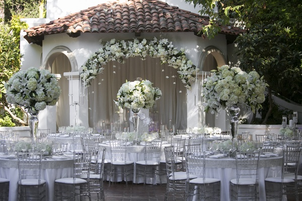 Outdoor Wedding Reception With White Flowers Clear Chairs And Silver Details