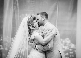 black and white photo of first kiss as husband and wife ashley alexiss travis yohe wedding portrait
