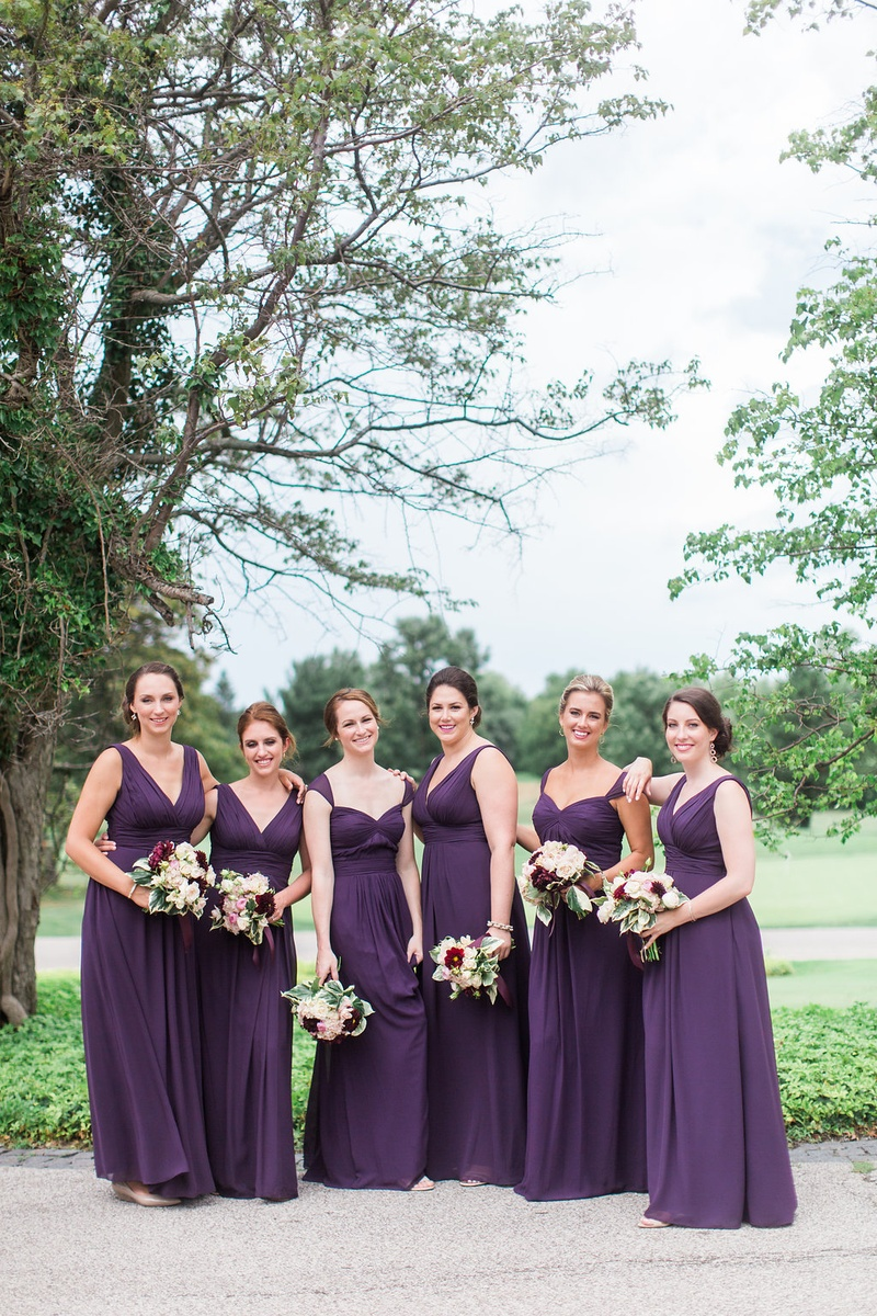 Bridesmaids in floor length purple eggplant bridesmaid dresses mismatched necklines bouquets