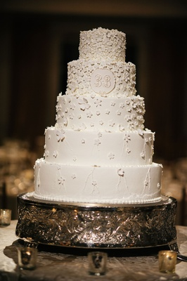 Five layer traditional white wedding cake with sugar flowers design on white cake monogram on tier