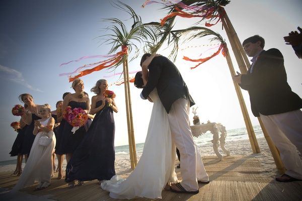 Couple kissing on sand at beach wedding
