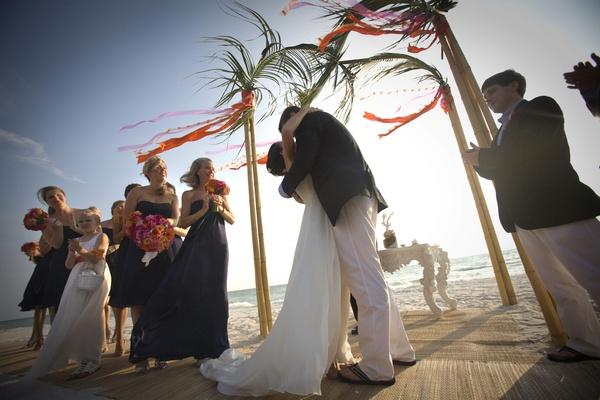 Couple Kissing On Sand At Beach Wedding