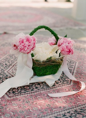 Grass basket with petals on Persian rug