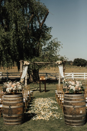 ceremony at saddlerock ranch with wine barrels at the base of aisle with flower petals