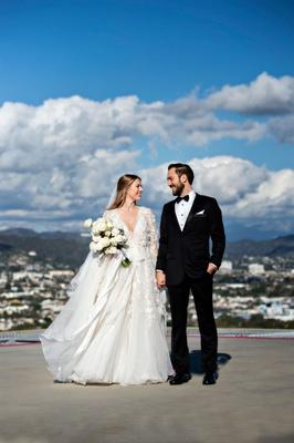 bride in marchesa long sleeve wedding dress and groom in tuxedo long hair portrait helipad rooftop