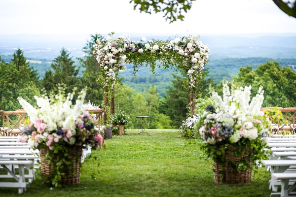 outdoor wedding ceremony with view of hudson valley white bench white pink purple flowers greenery
