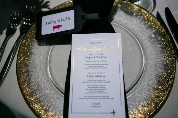 a couples dinner menu next to place card with small pink cow gold rimmed charger plate