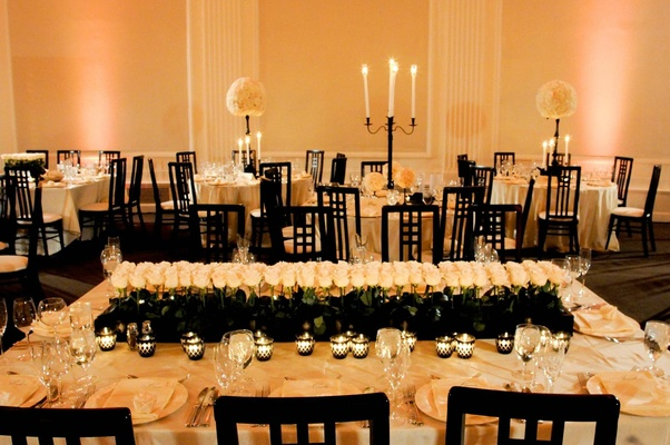 Rectangular table topped with votives and roses