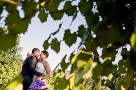 Bride in strapless wedding dress hugging groom portrait through leaves artistic wedding photo purple