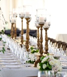 Tented reception with ornate candleholders lined amid white & pink rose table runner