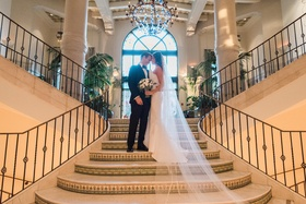 bride and groom touching forehead on the stairs of casa del mar