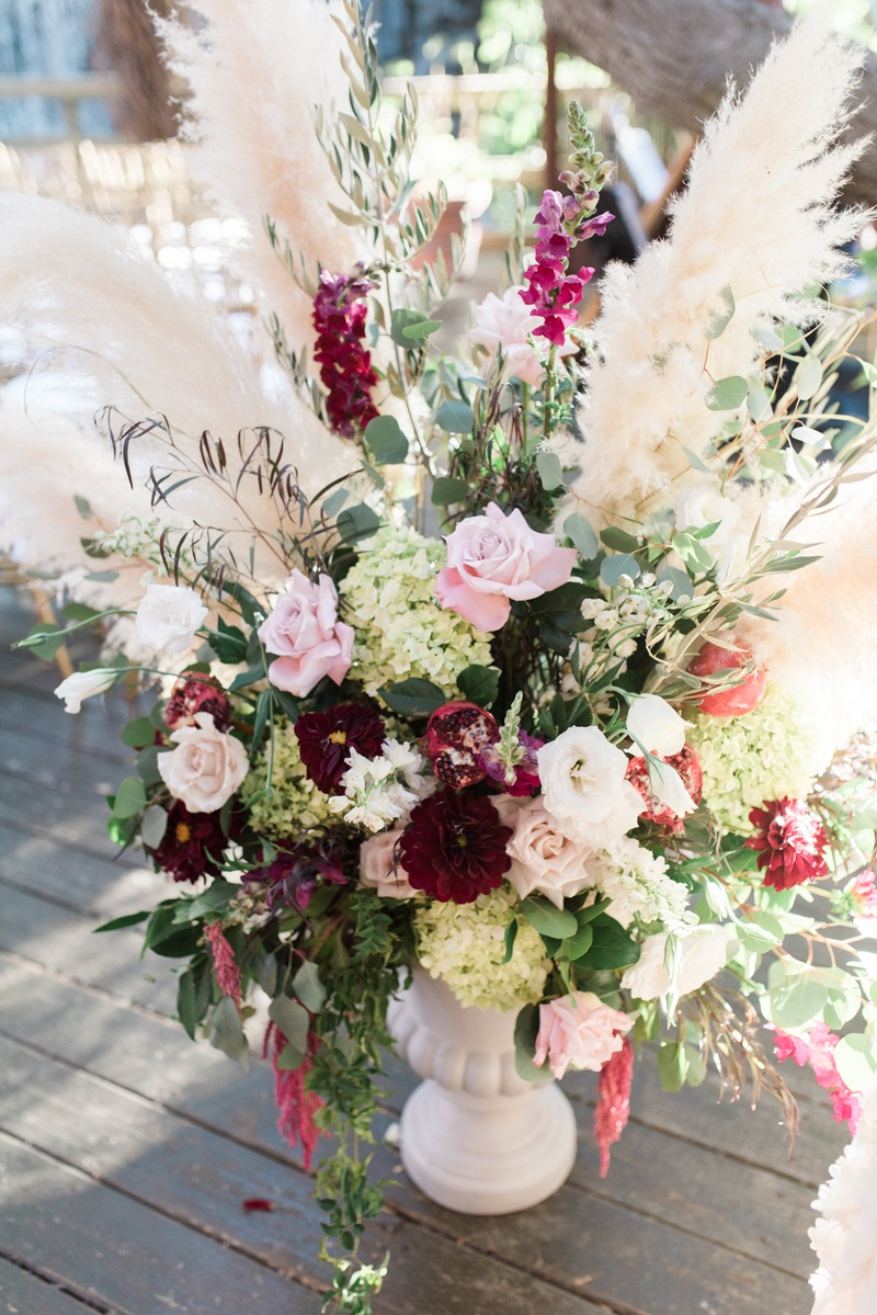 wedding ceremony flower arrangement with wine colored flowers and pampas grass