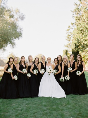 bride in martina liana ball gown, bridesmaids in black monique lhuillier dresses with v-neck