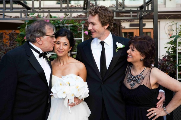 Couple smiling with father- and mother-of-the-bride