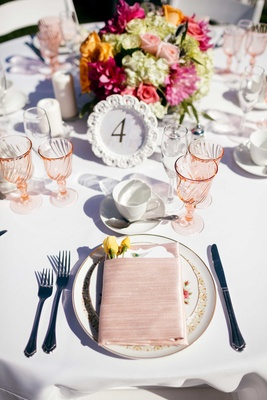 pink wine glasses, pink napkins, pink tableware, table number