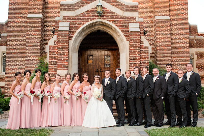 Bride And Groom In Front Of Church With Bridesmaids Groomsmen