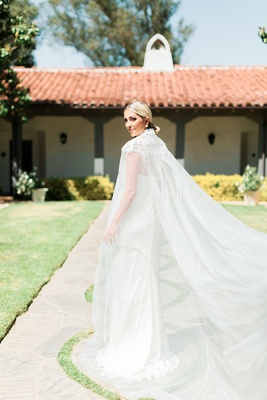 bride with low ponytail in slim sheath dress paired with long cape